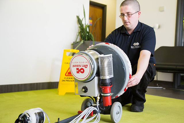 Man in Flawless Cleaning Ltd uniform fixing his carpet washing machine