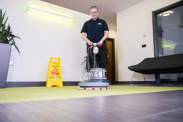 Man in Flawless Cleaning Ltd uniform washing a green office carpet