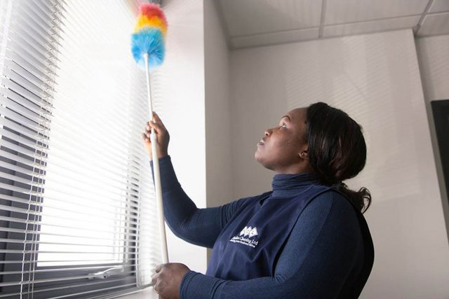 Woman with Flawless Cleaning Ltd uniform dusting window blinds