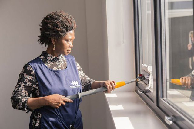 Woman with Flawless Cleaning Ltd uniform washing windows